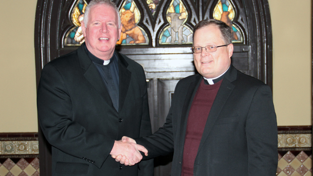 Jesuit Father James Fleming (left), president of Wheeling Jesuit University, greets Roman Catholic High School President Father Joseph Bongard.