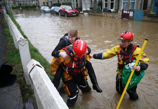 Members of the emergency services rescue a woman from a flooded property in York City Center in northern England. (CNS photo/Andrew Yates, Reuters)