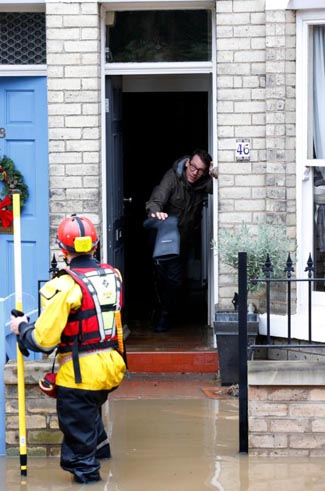 Rescue service workers evacuate a resident from his flooded home in York, England. Pope Francis called on Christians to pray for victims of several natural disasters that have hit parts of the United States, Great Britain and Paraguay. (CNS photo/Lindsey Parnaby, EPA)