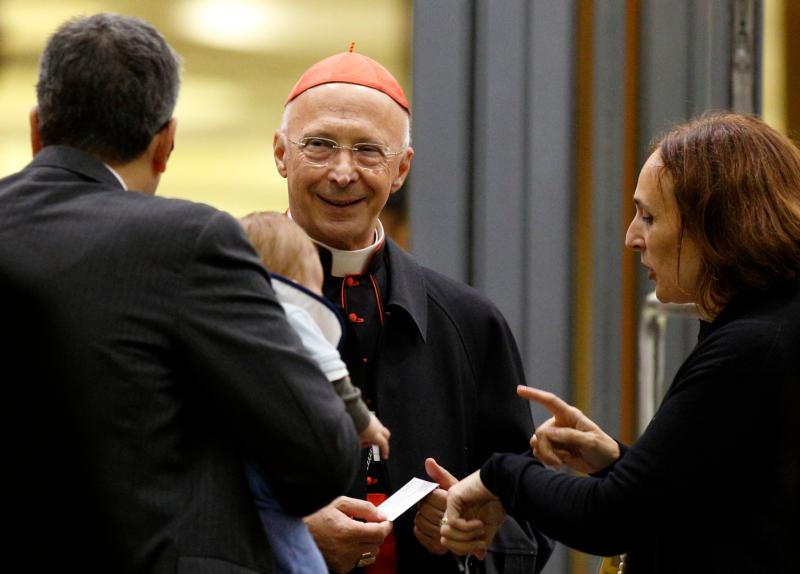 Cardinal Angelo Bagnasco, president of the Italian bishops' conference, talks with a married couple as they leave the opening session of the Synod of Bishops on the family at the Vatican in this Oct. 5, 2015, file photo. Cardinal Bagnasco said Italy's bishops are united in reaffirming the rights of children to be raised by a mother and father. His comment came as the Italian Senate is set to vote Jan. 28 on legislation that would allow civil unions for heterosexual and homosexual couples. (CNS photo/Paul Haring)