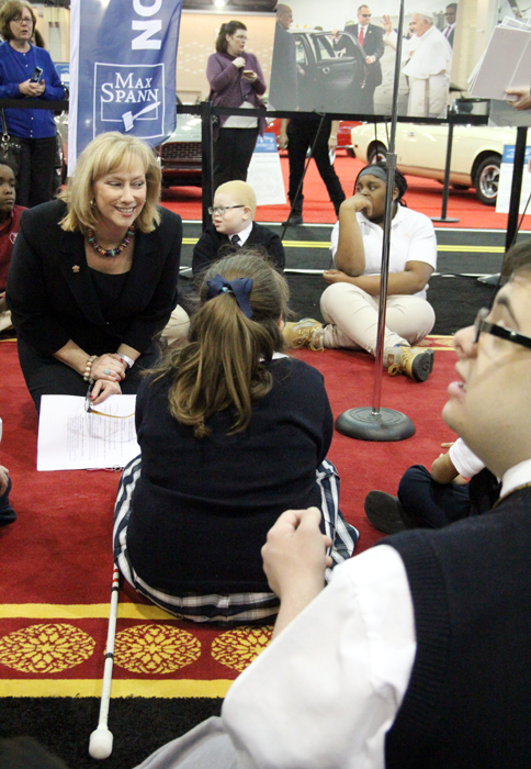 Donna Farrell, Executive Director for the World Meeting of Families – Philadelphia 2015, chats with approximately 20 students from the Archdiocesan Schools of Special Education while sitting on the red carpet Pope Francis walked on while in Philadlephia.