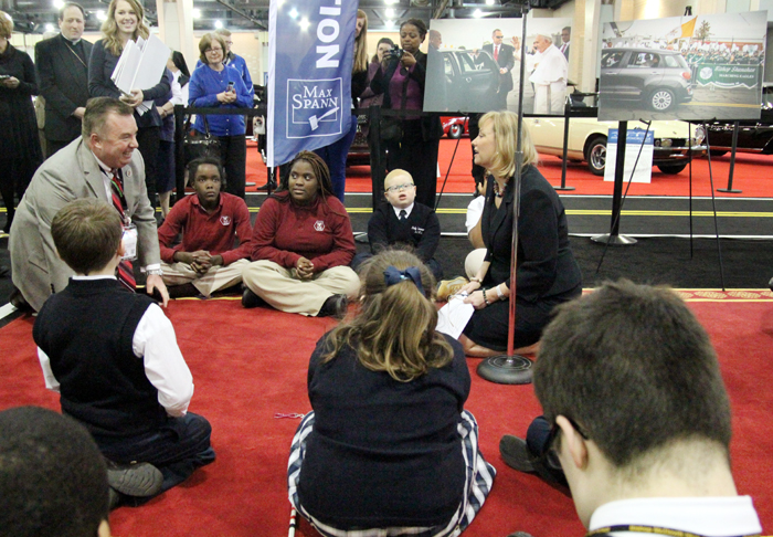 David Kelleher, Chairman of the 2016 Philadelphia Auto Show and Donna Farrell, Executive Director for the World Meeting of Families – Philadelphia 2015, along with approximately 20 students from the Archdiocesan Schools of Special Education sit on the red carpet walked on by Pope Francis while in Philadelphia.