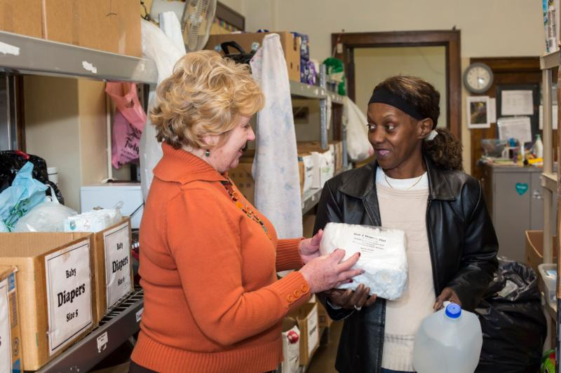 Vicky Schultz, president and CEO of Catholic Charities of Shiawassee and Genessee counties in Flint, Mich., hands diapers and bottled water to Deborah Nettles Jan. 19. Michigan Gov. Rick Snyder said he has failed Flint residents but pledged to take new steps to fix the city's drinking water crisis, starting with committing millions in state funding. (CNS photo/Jim West)