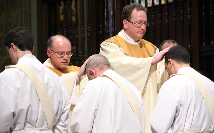 Father Steven DeLacy, director of the archdiocesan vocations office, sees the fruit of his labors and God's call of young men to ministry as he lays hands on newly ordained priests in May 2015.