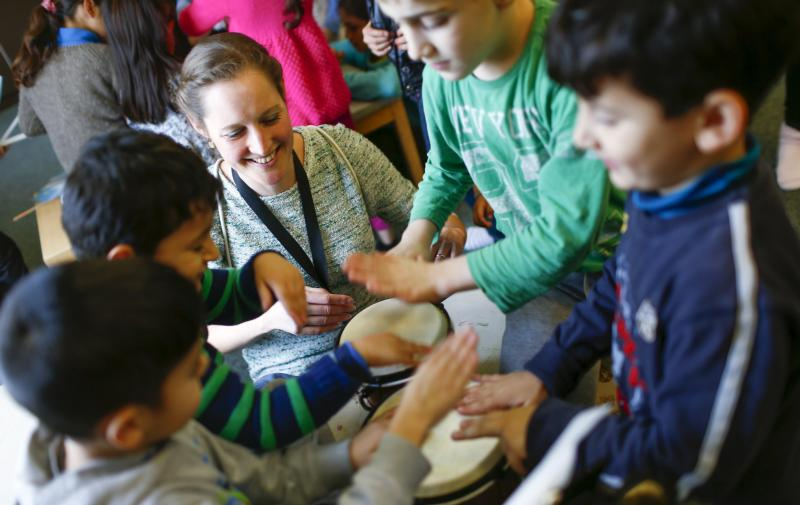 A volunteer plays drums with migrant children Jan. 26 at a refugee shelter in Berlin. Catholic bishops in Germany and Austria urged their countries to continue accepting refugees, despite demands for new restrictions after New Year's Eve violence in Cologne and other cities. (CNS photo/Hannibal Hanschke, Reuters)