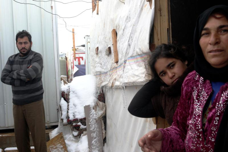 Syrian refugees stand in snow outside their tents Jan. 2 in Lebanon's Bekaa Valley. Lebanon continues to bear the brunt of absorbing massive numbers of refugees. (CNS photo/Lucie Parsaghian, EPA)