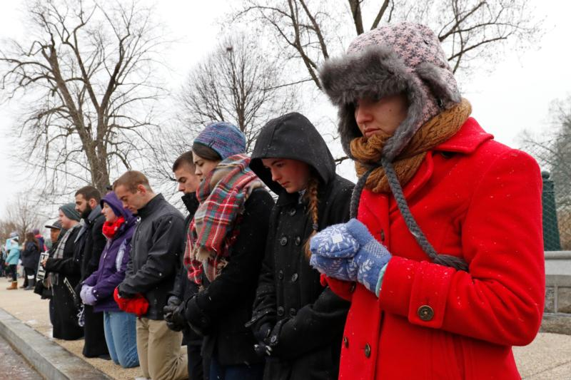 Pro-life advocates pray across from the Supreme Court building during the March for Life in Washington Jan. 22, the 43rd anniversary of the Supreme Court's Roe v. Wade decision legalizing abortion in the U.S. (CNS photo/Gregory A. Shemitz)