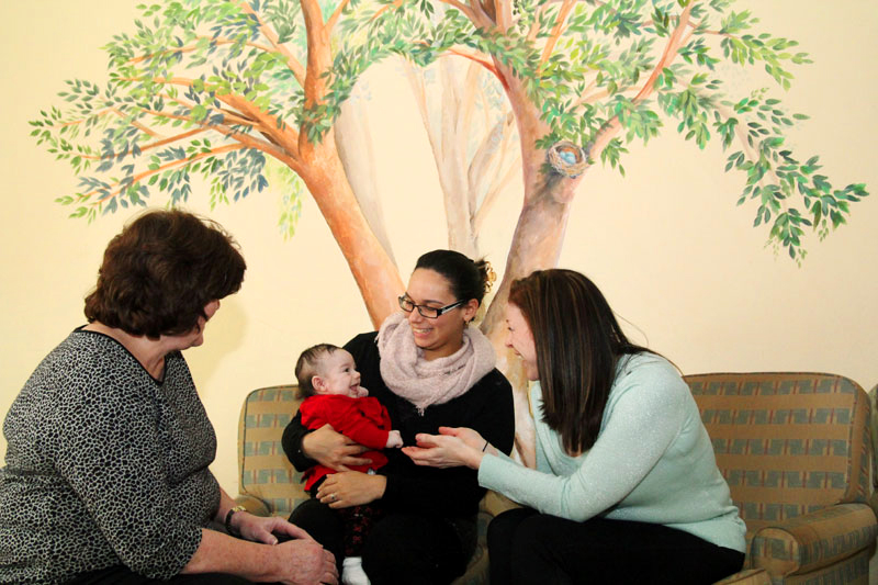 Hannah Kaskey and her daughter Sabrina are all smiles while they sit and chat with Ann Marie Welsh, program supervisor, and Brigid Risko, executive director, in the sitting room at Mother's Home in Darby, Delaware County.