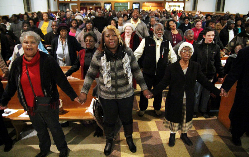 A standing room only crowd join hands and sing We Shall Overcome in home of Martin Luther King, Jr..