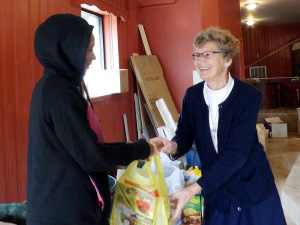 Sr Ann Raymond Welte, IHM hands a bag of groceries over to a woman from the community.