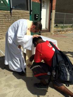Father Liam Murphy offers a blessing on the Kensington sidewalk.