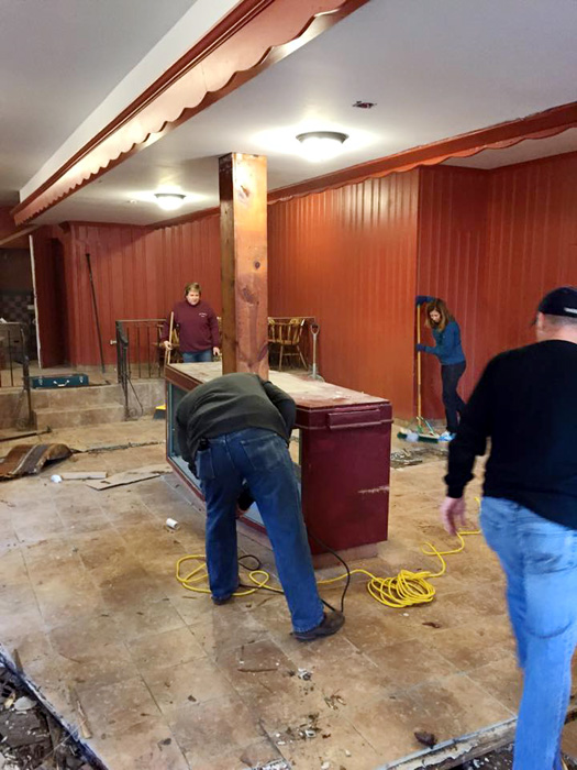 Volunteers work to replace a bar with an altar at Mother of Mary House.
