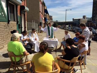 Fathers Liam Murphy and Joseph Devlin celebrate Mass on the Kensington sidewalk.