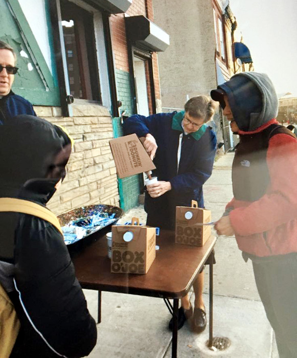 Father Liam Murphy and Sr Ann Raymond Welte, IHM chat with people as they offer coffee as the weather gets cold.