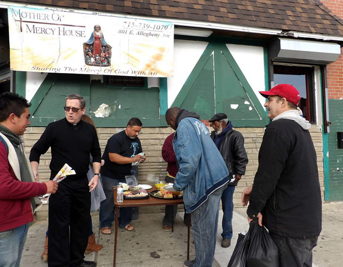 Father William Murphy speaks with residents of the Kensington neighborhood who share hoagies and snacks at Mother of Mercy House.