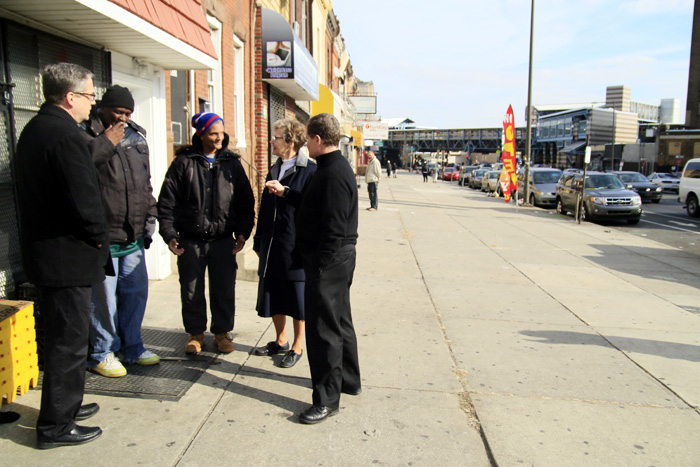 Father Liam Murphy, Sr Ann Raymond and Father Joseph Devlin chat with two men from the Kensington community.