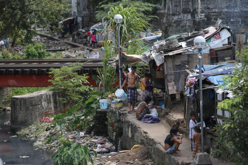 People are seen outside their makeshift homes by a polluted creek in Manila, Philippines. Speakers at the 51st International Eucharistic Congress in Cebu called on the faithful to remember to help the poor and suffering. (CNS photo/Mark R. Cristino, EPA)