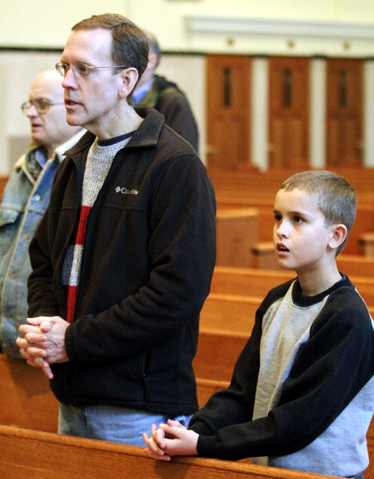 Father and son Jim and Reece Fitzpatrick from St Francis Xavier (The Oratory) pray together at Mass.