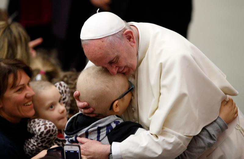 Pope Francis embraces a child as he meets the disabled during his general audience in Paul VI hall at the Vatican Jan. 13. (CNS photo/Paul Haring)