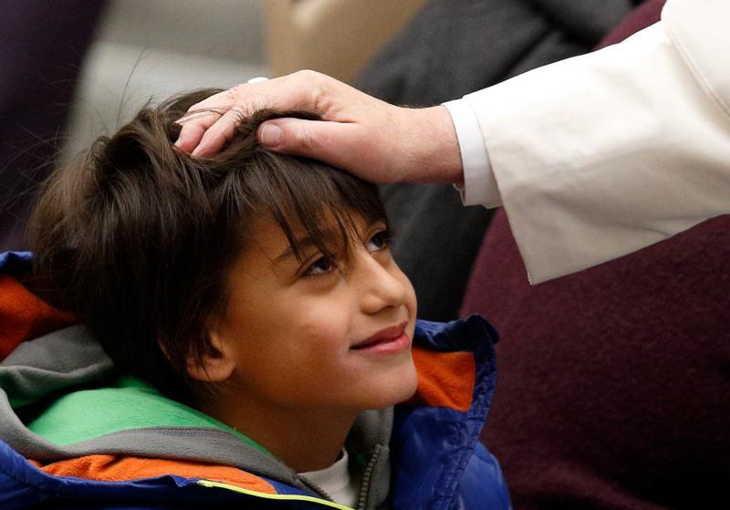 Pope Francis greets a child while meeting the disabled during his general audience in Paul VI hall at the Vatican Jan. 20. (CNS photo/Paul Haring)