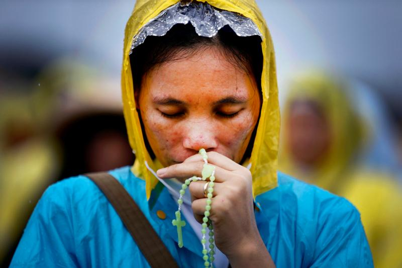 A woman prays in 2015 as Pope Francis celebrates Mass in Manila, Philippines. The prayers of the faithful, not the pope, bishops, priests or nuns, have the power to make miracles happen in the most impossible situations, Pope Francis said at his morning Mass. (CNS photo/Dennis M. Sabangan, EPA)