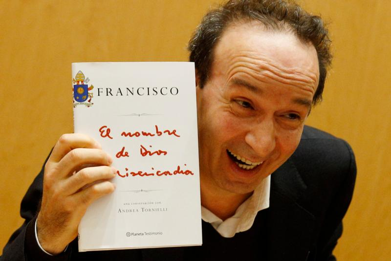 "Italian actor Roberto Benigni holds a copy of the book, ""The Name of God Is Mercy,"" during its presentation to journalists in Rome Jan. 12. The book is compiled from an interview Pope Francis did with Italian journalist Andrea Tornielli. (CNS photo/Paul Haring)"