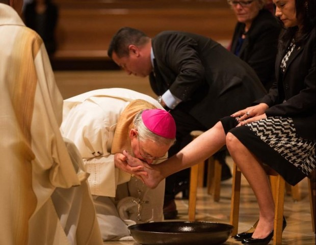 Los Angeles Archbishop Jose H. Gomez kisses the foot of a woman during Holy Thursday Mass in 2014 at the Cathedral of Our Lady of the Angels in Los Angeles. Following a request by Pope Francis, the Vatican issued a decree Jan. 21 specifying that the Holy Thursday foot-washing ritual can include women. (CNS photo/Victor Aleman, Vida Nueva)
