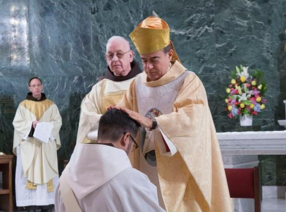 Archbishop Roberto Octavio Gonzalez Nieves of San Juan, Puerto Rico, lays his hands on the head of Franciscan friar Michael Reyes, during his Jan. 16 ordination at St. Francis of Assisi Church in in the Manhattan borough of New York. (CNS photo/Octavio Duran)