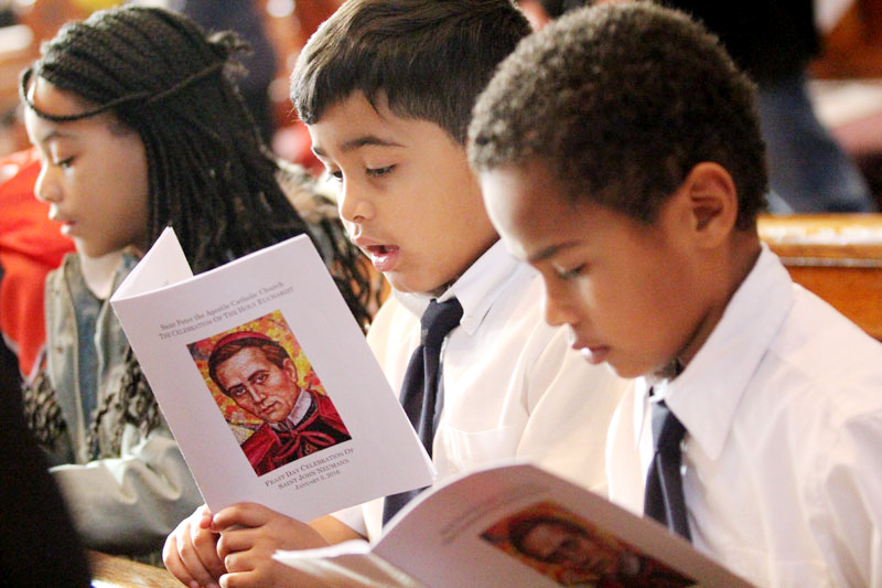 Hassan Jackson (center) and Otis Shenk (right), second grade students at St. Peter the Apostle School, sing during Mass at St. John Neumann's feast day Mass on Tuesday, Jan. 5. (Photo by Sarah Webb)