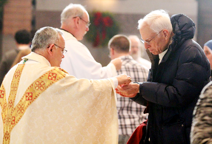 Arcbishop Charles Chaput distributes communion to Charles Hergenroeder from Saint Mary in Annapolis, Maryland.