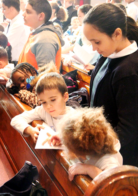 Sixth grader Alina Pavia helps kindergardeners Nolan Pustina and Victoria Green follow along in the Mass booklet.
