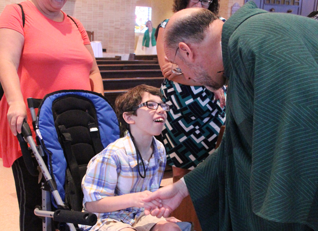 Father Edward Hallinan (right), pastor of St. John Chrysostom Parish in Wallingford, greets Cameron Sperduto and his mom, Leann, after the monthly Mass for persons with disabilities in September last year at the church in Delaware County.
