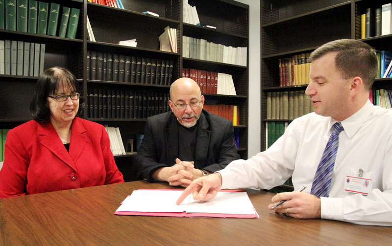 Staff at the Archdiocese of Philadelphias Metropolitan Tribunal -- from left, Janice Margerum (tribunal notary), Adam Dickerson (tribunal judge) and Msgr. Paul DiGirolamo (judicial vicar) -- review a case at the Archdiocesan Pastoral Center in Philadelphia. (Photo by Sarah Webb)