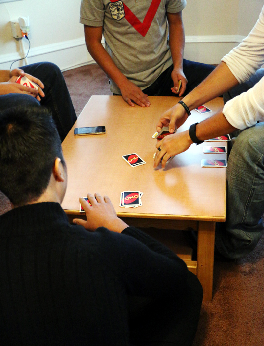 Some of the young men staying at Bridgewater Group Home play a card game. (Photo by Mark Cordero)