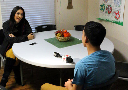 A reporter speaks with one of the young residents of a Catholic Social Services group home for unaccompanied minor refugees. (Photo by Mark Cordero)