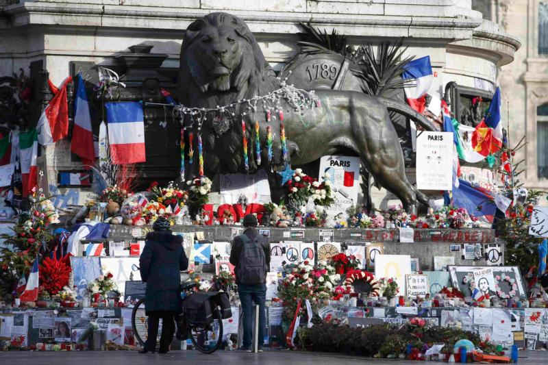 People at the Place de la Republique in Paris Jan. 6 look at flowers and messages paying tribute to the victims of last year's attacks at the office of the French weekly magazine Charlie Hebdo. (CNS photo/Charles Platiau, Reuters)