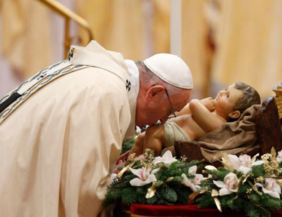 Pope Francis kisses a figurine of the infant Jesus at the start of Mass marking the feast of the Epiphany in St. Peter's Basilica at the Vatican Jan. 6. (CNS photo/Paul Haring)