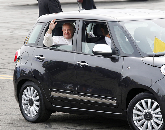Pope Francis rides in one of the Fiat 500L sedans as he arrives in Philadelphia Sept. 26, 2015. The car will be auctioned off Jan. 29 at the Philadelphia Auto Show. (Photo by Kevin Cook)