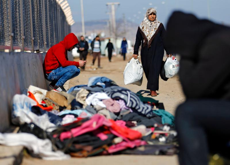 A refugee woman from Syria carries food while other displaced people sit near a border gate in Kilis, Turkey, Feb. 9. More than 30,000 people are stranded in northern Aleppo province after Turkish government forces closed border crossings. (CNS photo/Sedat Suna, EPA)