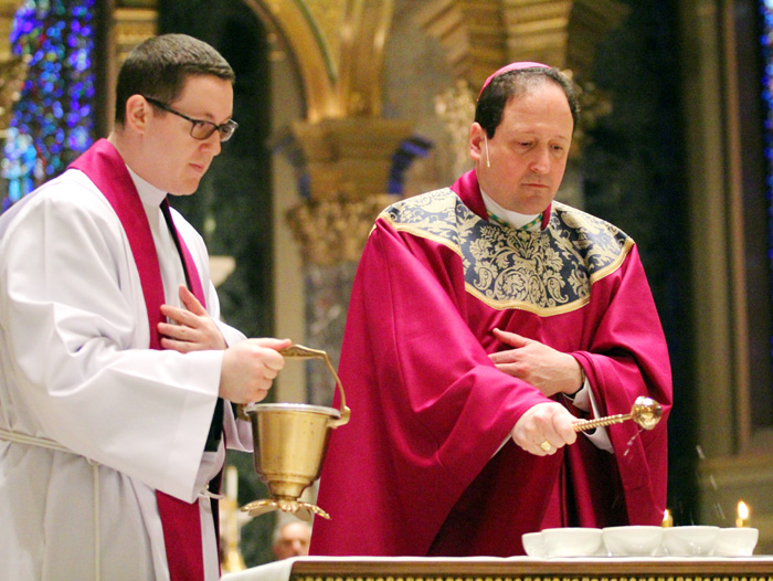 Father Kenneth Brabazon hold the holy water as Bishop John McIntyre blesses the ashes for distribution during Mass at The Cathedral Basillica of SS Peter and Paul on Ash Wednesday.