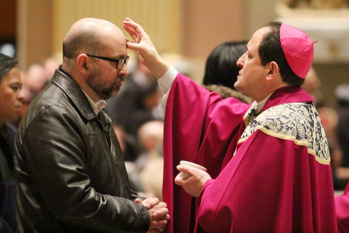Drew DeNardo, parishoner of Saint Catherine of Siena Parish in Horsham, receives ashes from Bishop John McIntyre.