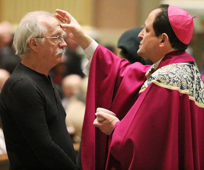 Bishop John McIntyre makes the symbol of a cross on Joe Percora, of Saint Francis of Assisi Church in Springfield, Delaware County, marking the beginning of the Season of Lent.