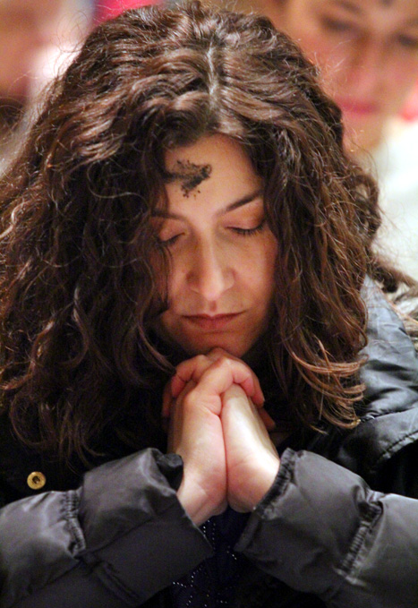 Jeannine Graff, from Epiphany of Our Lord Church in South Philadelphia, prays after receiving ashes.