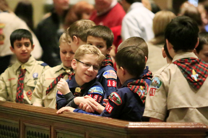 Young scouts offer one another a sign of peace.