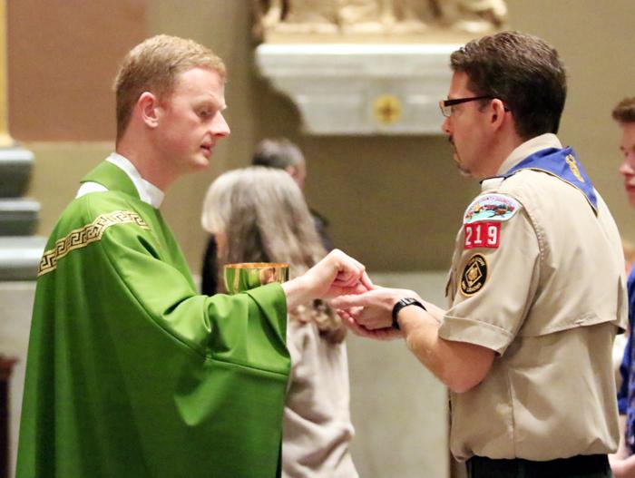 Boy Scout chaplain Father David Friel distributes holy communion.