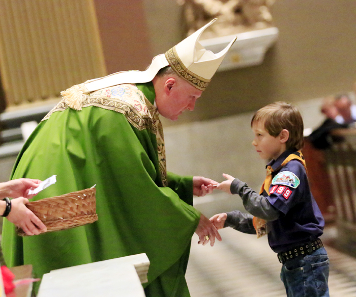 Kyle Kershaw, from Pack 199 St Agnes, shakes Bishop Fitzgerald's hand as he is given the Light of Christ Emblem.