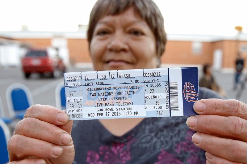 "A woman displays tickets to the Diocese of El Paso's ""Two Nations, One Faith"" event Feb. 15 outside St. Ignatius Church in El Paso. The event coincides with Pope Francis' Feb. 17 visit to El Paso's sister city, Cuidad Juarez, Mexico. (CNS photo/Nancy Wiechec)"