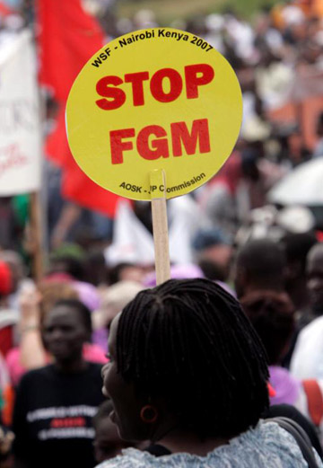 "A women in Nairobi, Kenya, holds a sign reading ""Stop Female Genital Mutilation"" in this Jan. 20, 2007, file photo. (CNS photo/Stephen Morrison, EPA)"