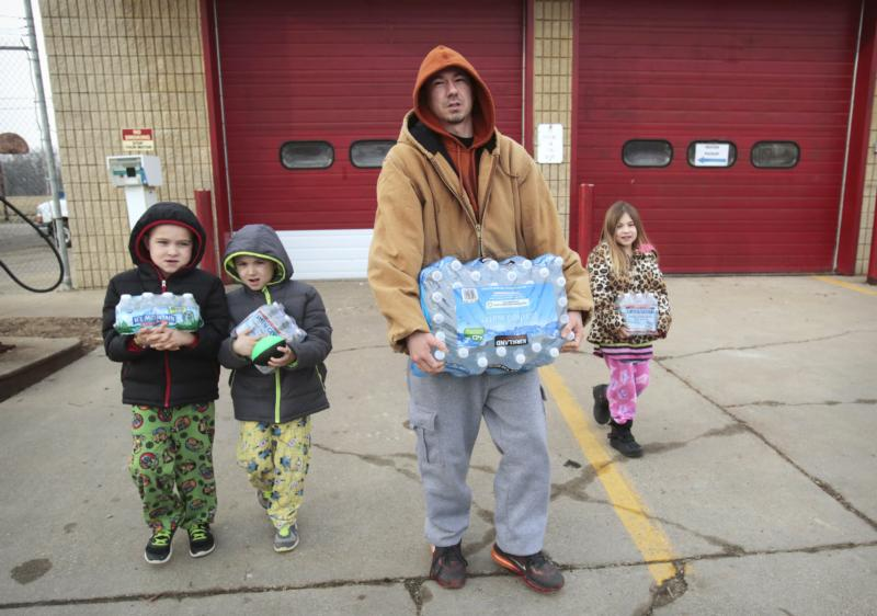 Flint resident Jerry Adkisson and his two children carry bottled water from a fire station in Michigan Feb. 7. (CNS photo/Rebecca Cook, Reuters)