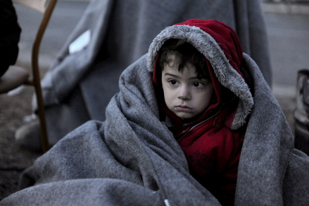 A migrant child is covered with a blanket as he and other refugees and migrants wait to cross the Greek-Macedonian border Jan. 28 near the village of Idomeni, Greece. (CNS photo/Alexandros Avramidis, Reuters)